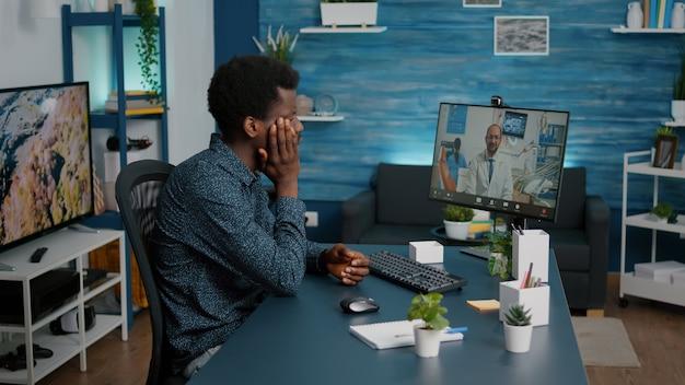 Чернокожий мужчина с зубной болью обращается за консультацией к стоматологу за консультацией по интернет-видеосвязи ...