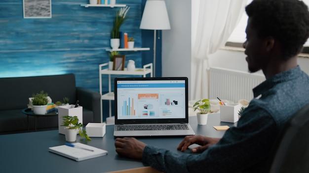 金融経済データアプリを使用して、自宅で仕事をしている黒人男性が居間からリモートで仕事をしている
