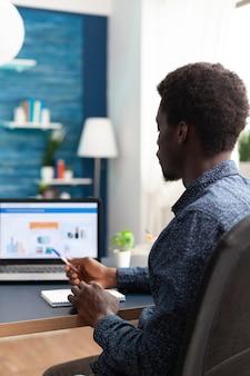金融経済データアプリを使用して在宅勤務の黒人男性