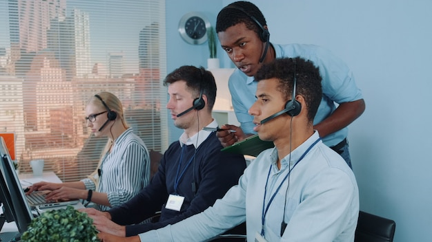 コールセンターで彼の同僚を助ける黒のマネージャーオペレーター