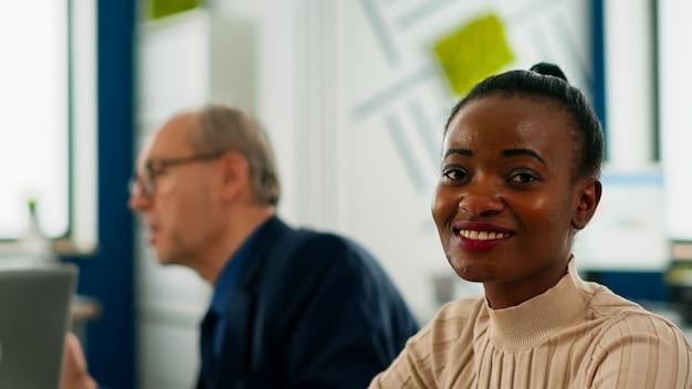 ブレーンストーミング中に会議デスクに座って、笑顔でカメラを見ている黒人マネージャーの女性。専門家で働く多様な起業家は、戦略会議の準備ができて金融ビジネスを開始します
