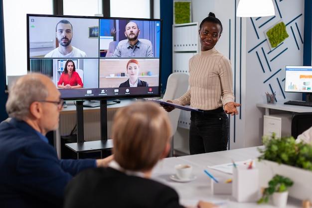 テレビ画面でビデオ通話でリモートの同僚と話し、新しいビジネスパートナーを提示する黒人マネージャーの女性