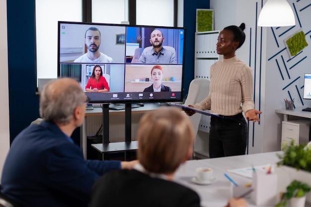 Donna manager nera che parla con colleghi in remoto in videochiamata sullo schermo della tv, presentando nuovi partner commerciali