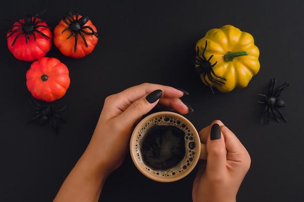 Черные ухоженные руки, держащие кружку капучино на фоне хэллоуина с преданными тыквами и пауками. вид сверху