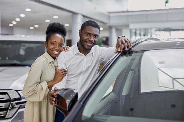 Черная замужняя семья смотрит на автомобиль в автосалоне