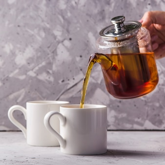 Black or masala tea in a teapot on gray
