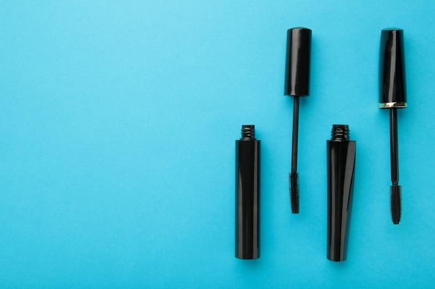 コピースペースと青い背景の上の黒いマスカラの杖とチューブ。上面図