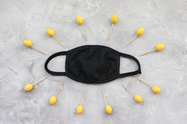 검은 마스크와 노란색 부활절 달걀