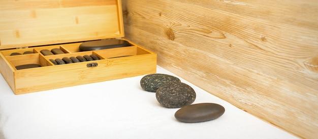 Черные массажные камни лежат возле деревянной коробки с массажными камнями на полотенце на столе.