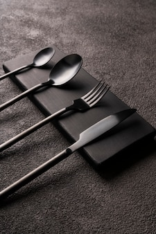 Black matte cutlery set-fork, spoon, knife, on dark concrete. minimalistic still life, stylish tableware. vertical photo close-up.