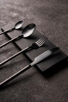 黒のマットカトラリーセット-フォーク、スプーン、ナイフ、暗いコンクリートの上。ミニマルな静物、スタイリッシュな食器。縦の写真のクローズアップ。
