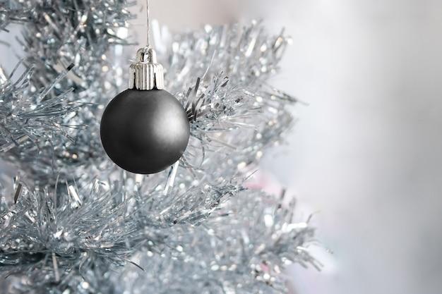 コピースペースを持つ銀の人工的なクリスマスツリー上の黒いマットな金属ボール