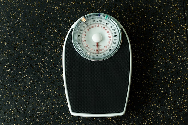 Black mechanical weight scale on the black floor with golden glitter. weight loss and sports