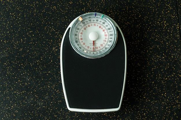황금빛 반짝이와 검은 바닥에 검은 기계식 체중 규모. 체중 감량 및 스포츠
