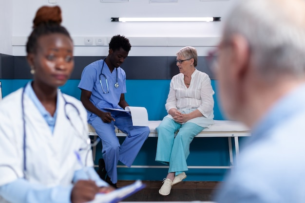 机に座って話している黒人の薬と白人の古い患者