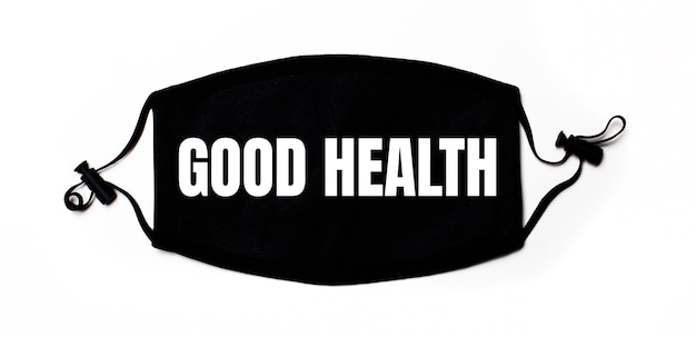 Black medical face mask on a light surface with the inscription good health