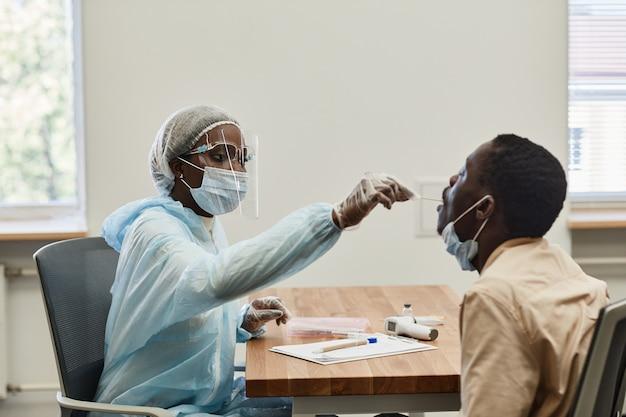 Черная медсестра в защитном костюме и маске просит пациентку открыть рот, чтобы она могла ...