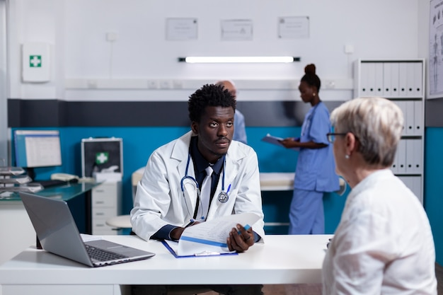Black medical specialist consulting elderly patient at desk