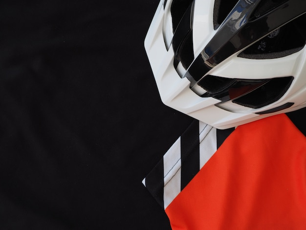 Black men's jersey and white bicycle helmet. sport accessories, sport equipment. top view. place for text.