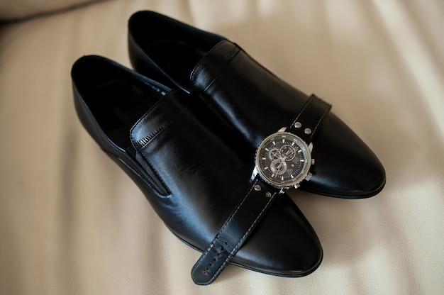 Черные мужские туфли и часы