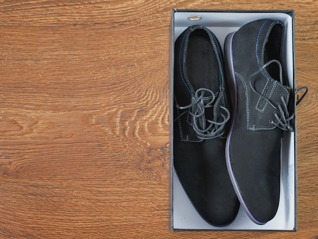 Black men's shoes in the box on the wooden floor.
