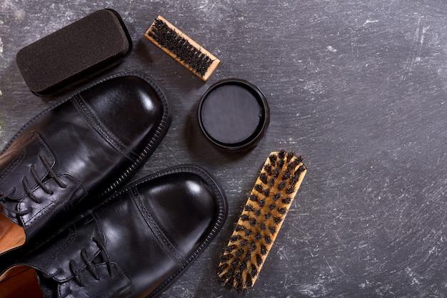 Черная мужская обувь с аксессуарами для ухода на темном, вид сверху