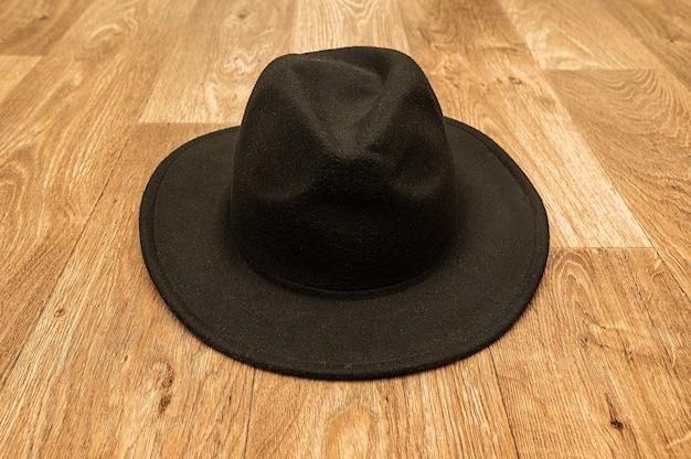 Черная мужская стильная фетровая шляпа. лежит на деревянном полу.