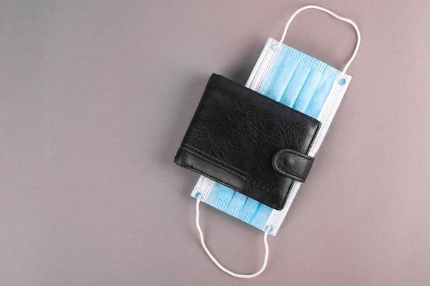 Черный мужской кошелек с медицинской маской.