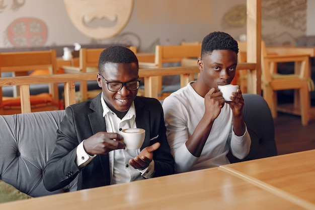 Black men sitting in a cafe and drinking a coffee