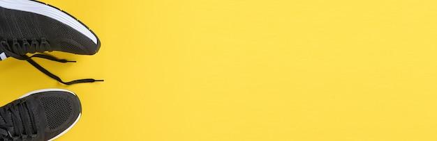 노란색 바탕에 흑인 남성 운동화입니다. 패션 블로그나 잡지 컨셉입니다. 남자 신발, 트렌디한 운동화, 패션, 라이프스타일. 조롱. 평면 평면도 복사 공간 최소한의 배경입니다.