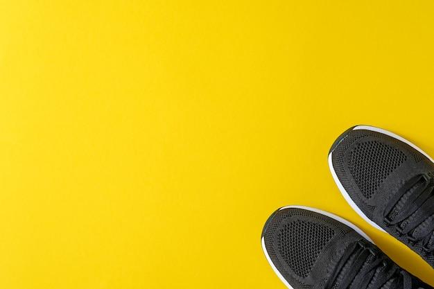 Черные мужские кроссовки на желтом столе. модный блог или концепция журнала. мужская обувь, модные кроссовки, мода, стиль жизни. плоский вид сверху копия пространства минимальный стол.