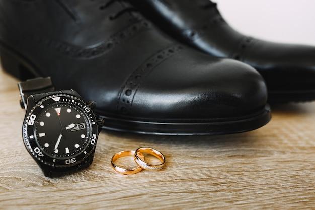 金の結婚指輪と機械式腕時計を備えた床の黒いメンズシューズ