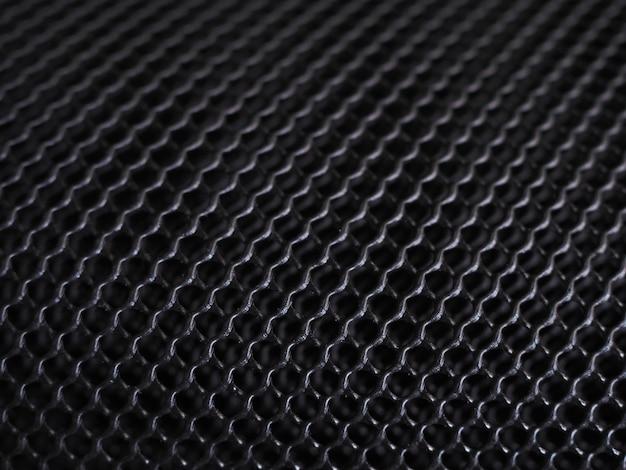 Black mesh grille, dark background with grid texture