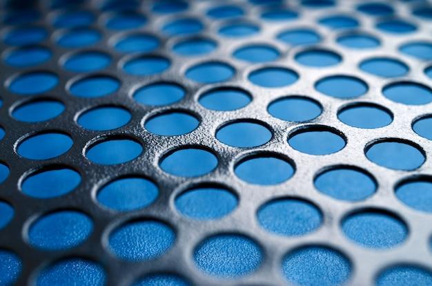 파란색 배경에 구멍이 검은 금속 컴퓨터 케이스 패널 메쉬 프리미엄 사진