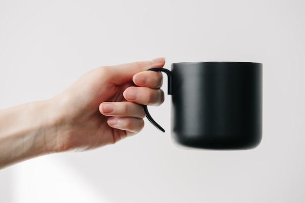 Черная металлическая чашка для чая и кофе в руке женщины
