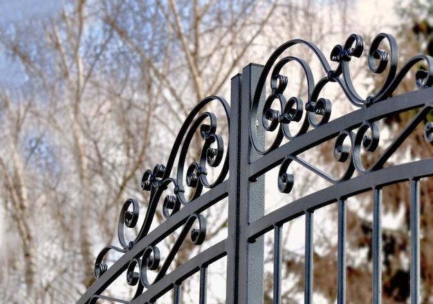 Черный металлический забор закрыт в частном саду
