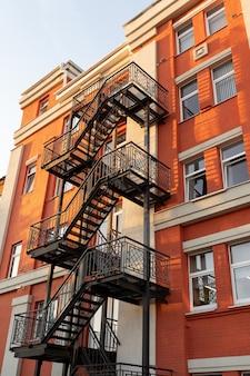 古いれんが造りの建物のセキュリティコンセプトの改修のファサードにある黒い金属製の非常階段