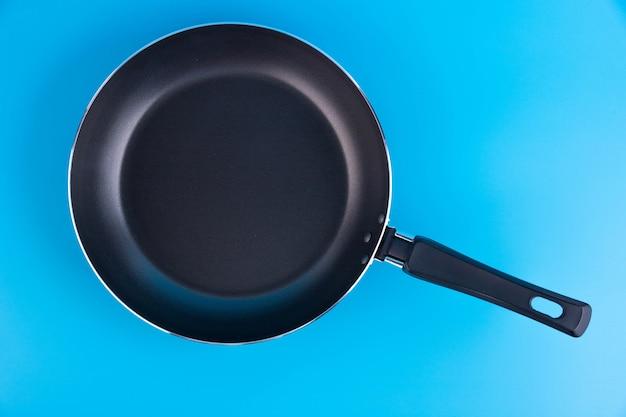 青い背景の上の黒い金属のフライパン。
