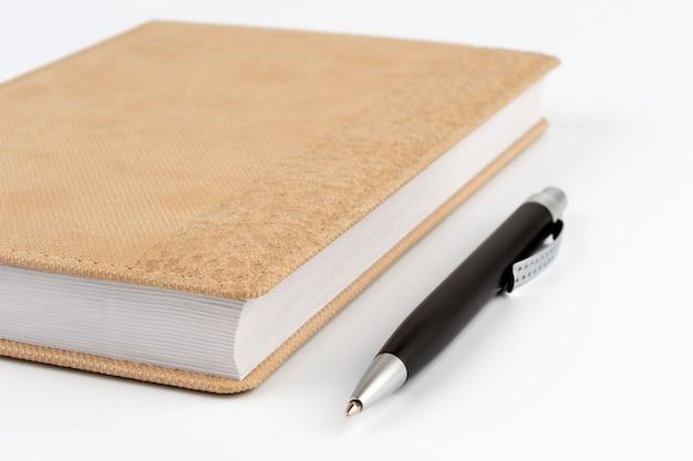 Черная металлическая ручка рядом с дневником бежевого цвета крупным планом