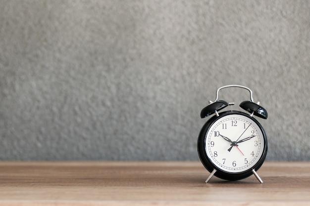 背景にコンクリートの壁と木製の机の上の黒い金属のレトロな目覚まし時計