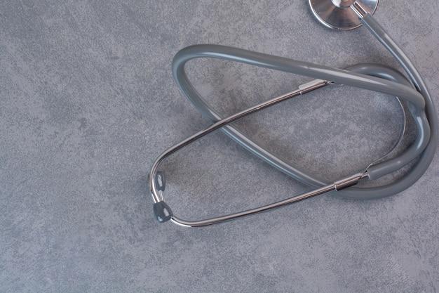 Black metal stethoscope on marble table.