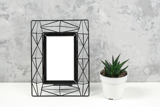 Черная металлическая вертикальная рамка с белым бланком и сочные цветы на столе на фоне серой бетонной стены