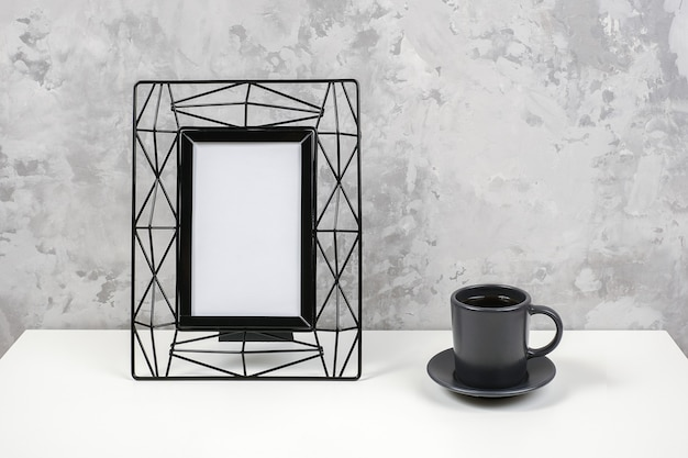 Black metal vertical frame with white blank and cup of coffee on table against grey concrete wall.
