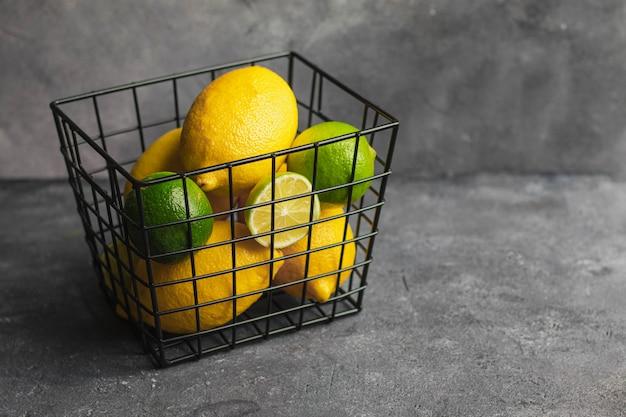 Черная металлическая коробка с цитрусовыми лаймом и лимоном на черном фоне камень. вид сверху с copyspace. продукт для повышения иммунитета. концепция витамина с. стимуляция иммунитета