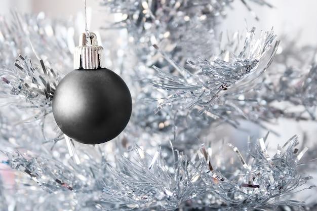 Черный металлический шар на серебряной искусственной елке