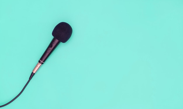 Black microphone on blue teal background