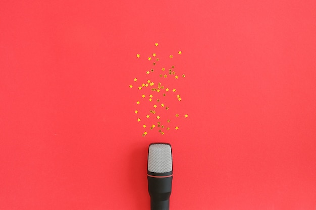 Black microphone and gold stars confetti on red background. concept music party or karaoke.