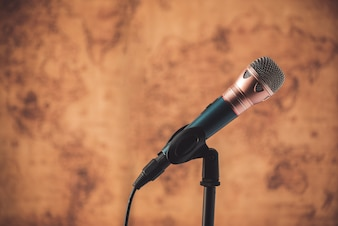 Black microphone with blurred old world map background