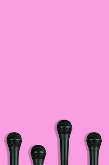 Black microphones pattern on pink background top view