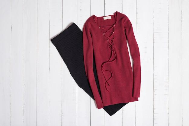 白い木製の床板にひもで締められた黒いミディスカートと赤いセーター